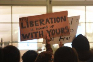 """Protester's sign at DIA reads """"My liberation is bound up with yours"""""""