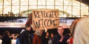 "Protesters hold ""Refugees Welcome"" sign"