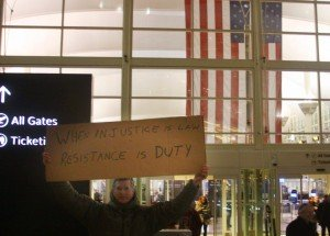 """Protester's sign at DIA reads """"When injustice is law, resistance is duty"""""""