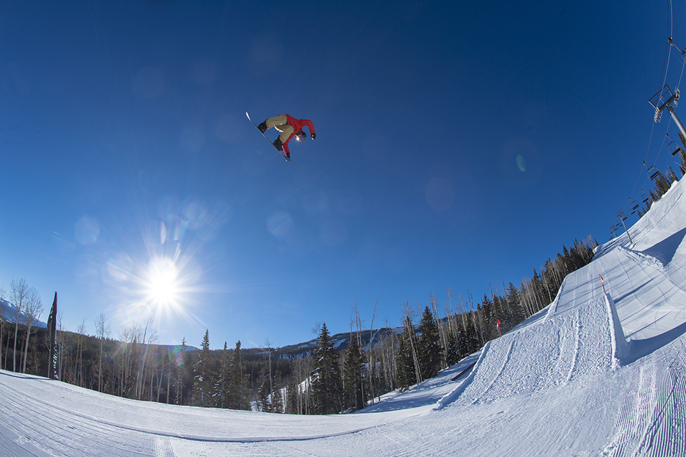 Robert Pettit jumping off big kickers in the terrain park while snowboarding in the mountains at Aspen Snowmass Ski Resort in Colorado