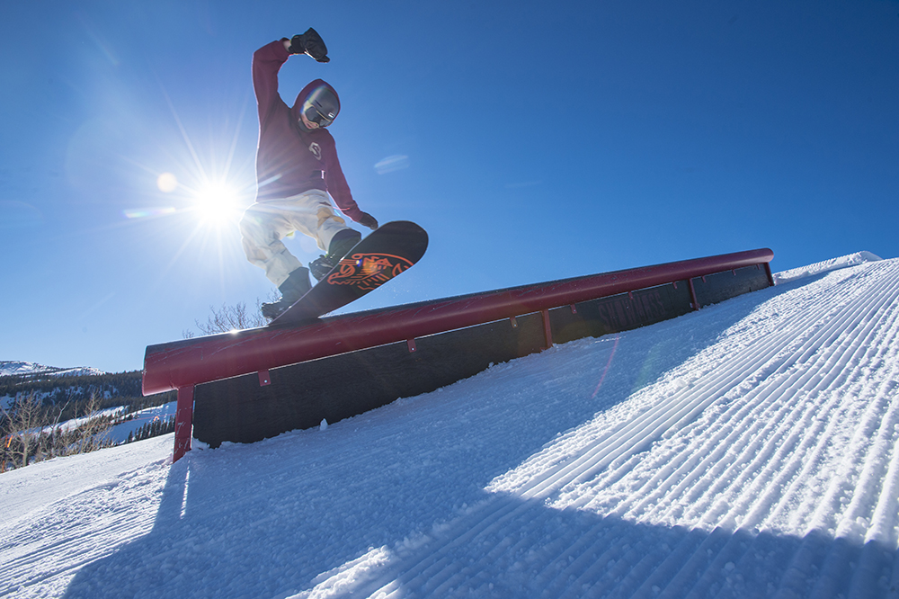Shane Serrano sliding down a metal rail in the terrain park while snowboarding in the mountains at Aspen Snowmass Ski Resort in Colorado