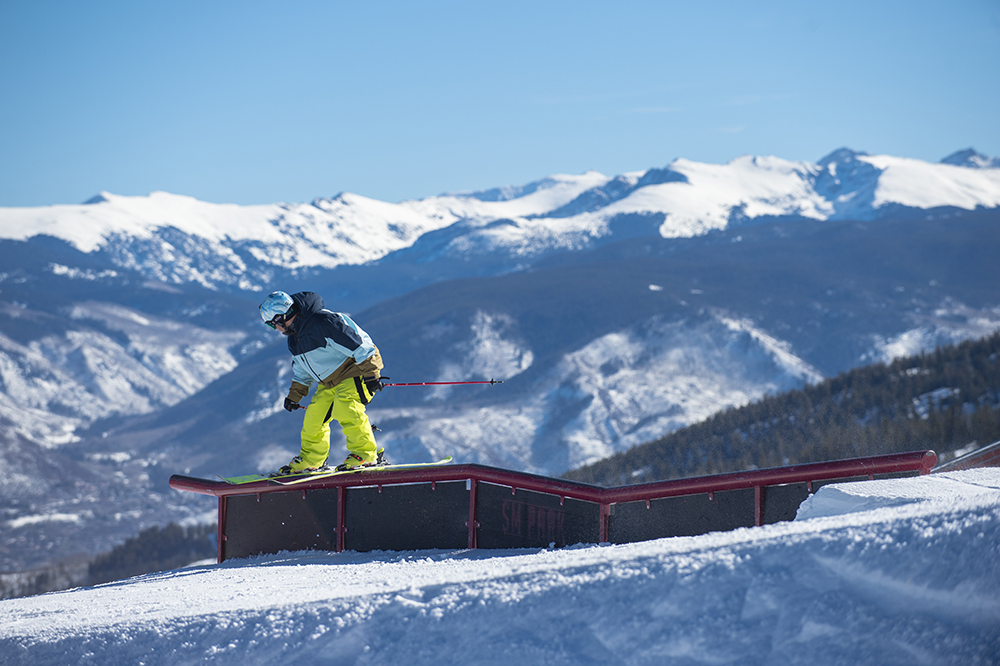 Tae Westcott sliding down a metal rail in the terrain park while skiing in the mountains at Aspen Snowmass Ski Resort in Colorado